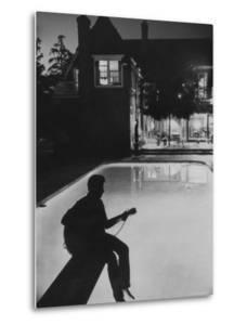 Pop Singer Ricky Nelson Sitting on Diving Board of Family Swimming Pool by Hank Walker