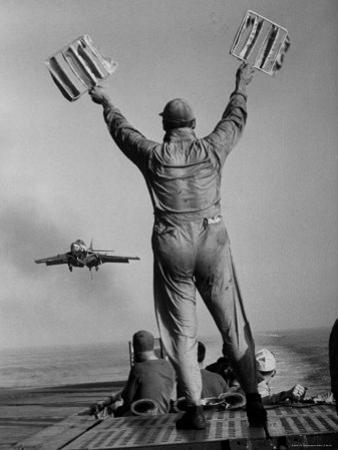 Shot of a Man Using Hand Lights to Signal an Incoming Aircraft Towards the Carrier's Landing