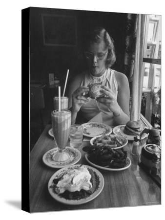 Teenaged Girl Sitting in Drugstore Eating a Hamburger