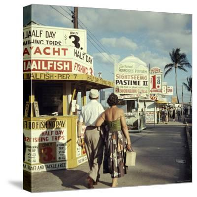 Vacationers Walking by Booths Advertising Boat Tours