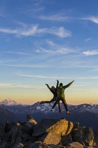 A Young Couple Jump On Top Of A Mountain During Sunset In The North Cascade Mountains Of Washington by Hannah Dewey