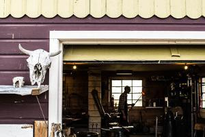 Blacksmith Carries Hot Iron Across His Workshop Towards A Power-Hammer by Hannah Dewey
