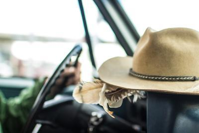 Cowboy Hat Sits On The Dash Of A Vintage Truck While A Man Drives