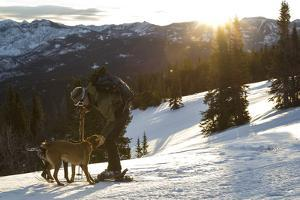 Man Shows His Dogs Affection Before A Morning Backcountry Ski In Montana's Gallatin Range by Hannah Dewey