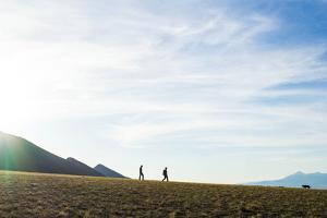Two Men Walk Down A Ridge Line With A Dog Running Towards Them by Hannah Dewey