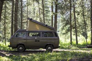 Volkswagen Bus Parked At A Campsite Along West Fork Of The Madison River In Montana During Summer by Hannah Dewey