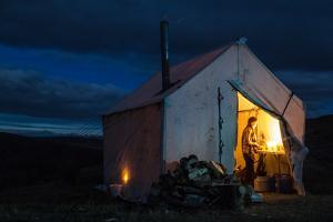 Woman Cooks Dinner By Candlelight In Her Wall Tent At Hunting Camp In Montana by Hannah Dewey