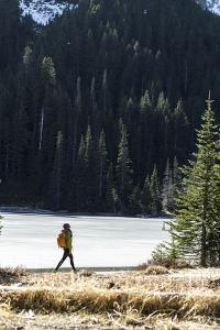 Woman Hiker Walks Alongside A Frozen Lake In The Olympic Mountain High Country During Winter In WA by Hannah Dewey