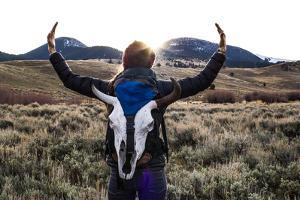 Woman Holds Her Arms Up Like Horns While Wearing A Bison Skull On Her Backpack by Hannah Dewey