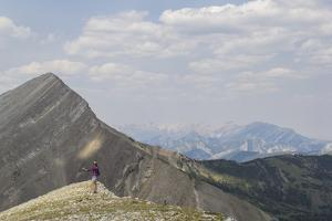 Woman Holds Out A Rock Cairn On Top Of A Mountain In Montana's Bob Marshall Wilderness by Hannah Dewey