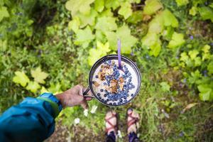 Woman Holds Out Her Breakfast Of Oats And Wild Huckleberries While Backpacking During The Summer by Hannah Dewey