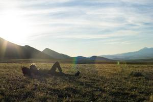 Woman Lays Down In The Grass Relaxing Amidst The Mountains And The Setting Sun by Hannah Dewey