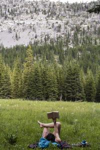 Woman Reads A Book In A Mountain Meadow In The Bob Marshall Wilderness In Montana During Summer by Hannah Dewey