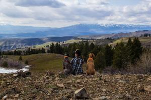 Woman Sits Next To Her Two Dogs Looking Out Into Idaho's Mountainous Landscape by Hannah Dewey