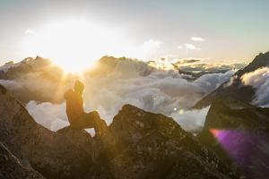 Woman Sits On A Mountain Peak Looking Into The Sun Rising In The North Cascades by Hannah Dewey