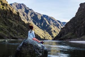 Woman Sits On A Rock Looking Out Into The Snake River In Hell's Canyon Idaho by Hannah Dewey