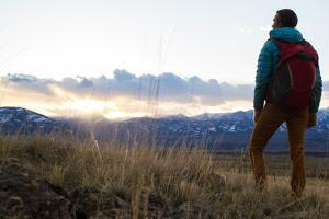 Woman Stands Looking Out Into Montana's Rocky Mountains With Her Hiking Backpack On by Hannah Dewey