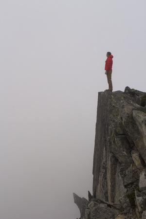Woman Stands Looking Out Into The Fog On Top Of A Cliff In The North Cascades, Wa