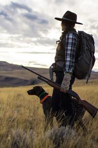 Woman Stands Next To Her Hunting Dog Looking Out Into Montana's Vast Landscape by Hannah Dewey