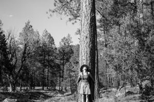 Woman Stands With Her Arms Wrapped Around A Ponderosa Pine Tree Looking Up And Smiling by Hannah Dewey