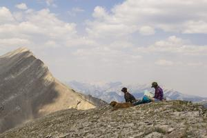 Woman Takes A Break From Hiking To Read A Map In Montana's Bob Marshall Wilderness by Hannah Dewey
