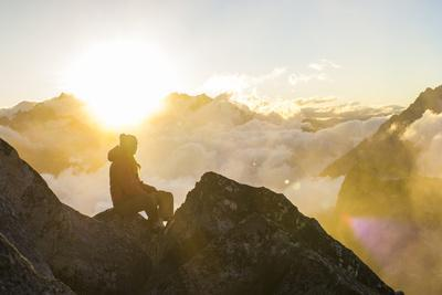 Woman Watches The Sunrise On Top Of A Mountain In North Cascade National Park In Washington