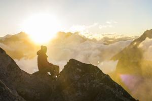 Woman Watches The Sunrise On Top Of A Mountain In North Cascade National Park In Washington by Hannah Dewey