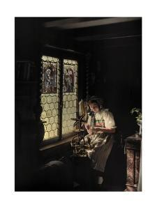 A Woman Works with Her Spinning Wheel in the Sunlight from the Window by Hans Hildenbrand