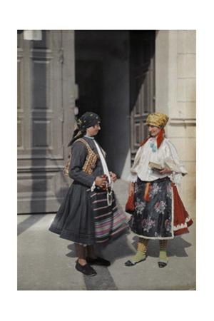 Two Serbian Women Stand in their Brightly Colored Clothes by Hans Hildenbrand