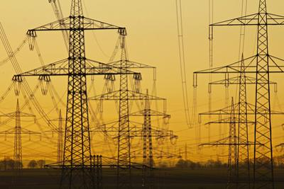 Pylons and power lines in morning light, Germany, Europe by Hans-Peter Merten