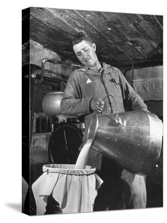 Man Straining Milk into a Can Through a Piece of Cloth