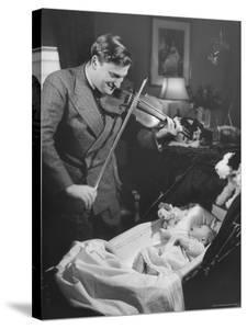 Violinist Yehudi Menuhin, Playing the Violin for His New Baby Daughter in Hotel Room by Hansel Mieth