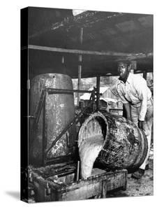 Worker Pouring Gum from Pine Trees into a Still During Turpentine Production by Hansel Mieth