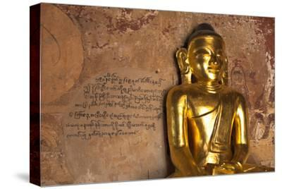 Golden Buddha Statue in Front of Burmese Writing on Wall, Bagan, Myanmar