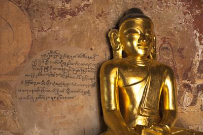 Golden Buddha Statue in Front of Burmese Writing on Wall, Bagan, Myanmar by Harry Marx