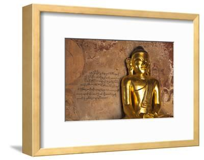 Golden Buddha Statue in Front of Burmese Writing on Wall, Bagan, Myanmar