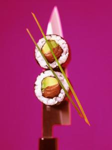 Two Maki-Sushi with Avocado and Salmon on Knife by Hartmut Kiefer