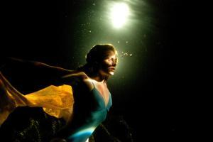 A Model Poses in a Pool with Dramatic Lighting by Heather Perry