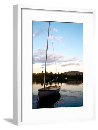 A Small Sailboat Anchored in a Pristine Lake