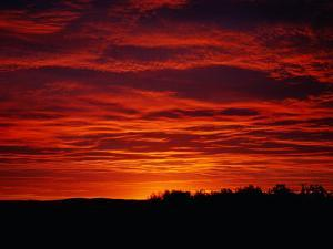 A Sunrise Bathes the Clouds in a Red Glow by Heather Perry