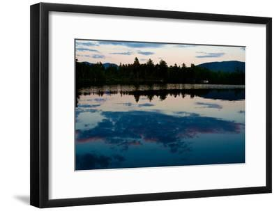 Clouds Reflect in a Scenic Pristine Lake, Lined with Evergreen Trees, at Sunrise