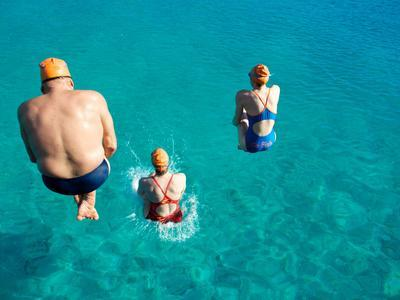 Three Open Water Swimmers Jumping into the Water