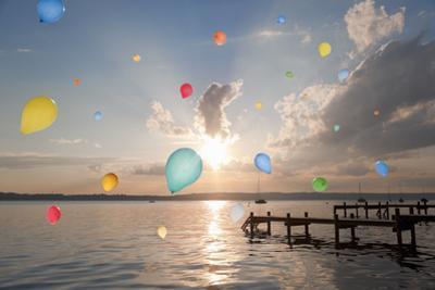 Balloons Floating over Still Lake