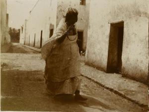 Voyage en Algérie : femme marchant dans une rue de Biskra by Henri Jacques Edouard Evenepoel