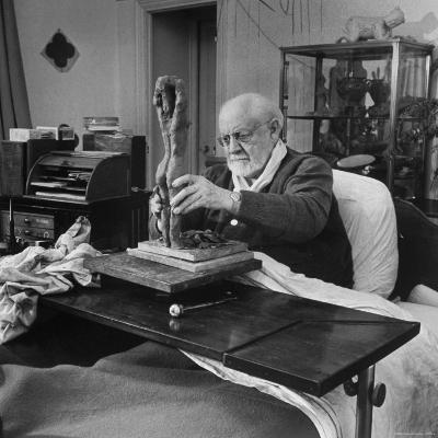 Henri Matisse Sculpting Nude Female Figure While Sitting in Bed in His Apartment-Dmitri Kessel-Premium Photographic Print