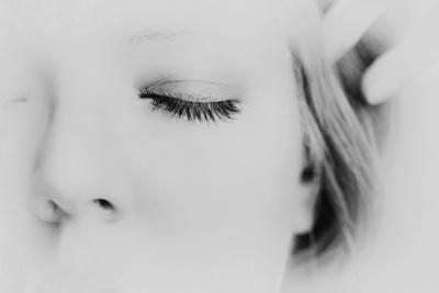 Close-Up of One Side of Young Woman's Face with Focus on the Eyelashes of Her Closed Eye