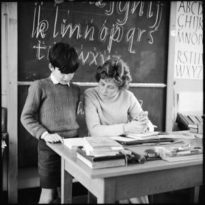 A Boy Pupil Reading with His Teacher, at Her Desk in Front of the Blackboard by Henry Grant