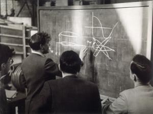 A Group of Scientists Study a Problem by Using Diagrams on a Blackboard by Henry Grant