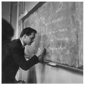 A Teacher Writing on a Blackboard at Northfield House Junior School, Leicester by Henry Grant