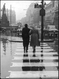 A Typical English Street on a Rainy Shopping Day: an Elderly Couple Use the Zebra Crossing by Henry Grant